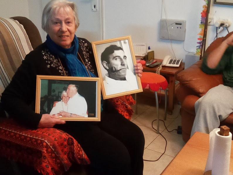 מרים מראה תמונותיו של אושי בן זוגה ובעלה במשך הרבה שנים